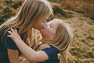 Two cute blond sisters kissing outdoors - NMSF00102