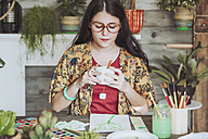 Young woan drinking tea and lookig at her paintings of plants - RTBF00851