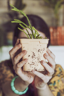 Young woman holding freshly potted cactus - RTBF00881