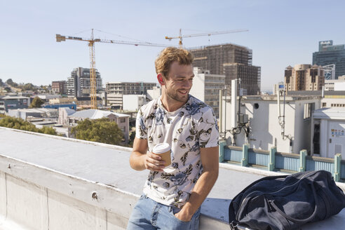 Young man standing on rooftop terrace drinking coffee - WESTF23064