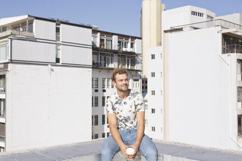 Young man stitting on rooftop terrace drinking coffee - WESTF23067