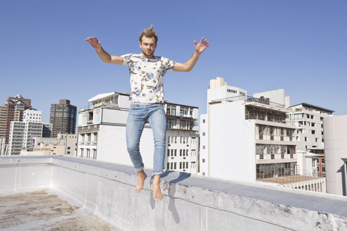 Barefooted man jumping from balustrade of a rooftop terrace - WESTF23070