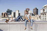 Young couple sitting on balustrade of a rooftop terrace, using smartphone - WESTF23082