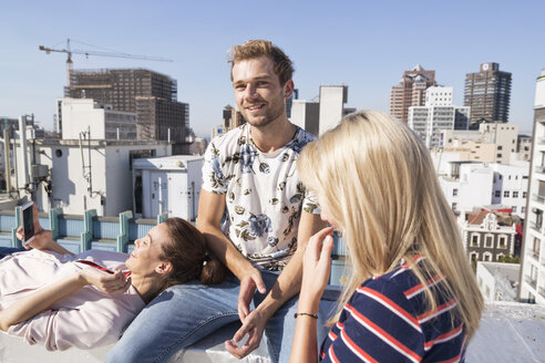 Friends meeting on a rooftop terrace in summer, woman using smartphone - WESTF23085