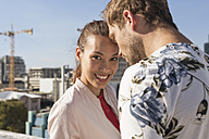 Young couple flirting on a rooftop terrace - WESTF23091