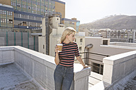 Young woman drinking coffee on a rooftop terrace - WESTF23097