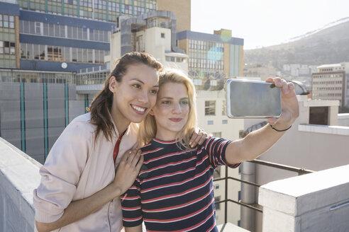 Friends taking selfies on a rooftop terrace - WESTF23100