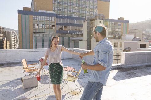 Young couple celebrating on a rooftop terrace, dancing together - WESTF23109