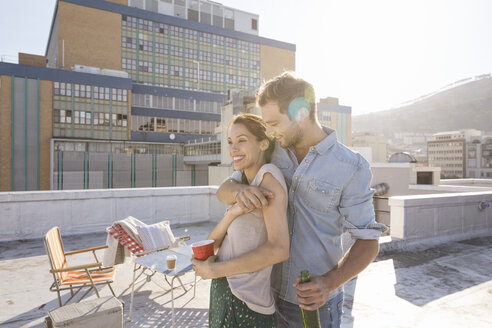 Young couple celebrating on a rooftop terrace, embracing at sunset - WESTF23112
