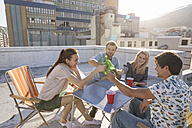 Friends having a rooftop party on a beautiful summer evening - WESTF23118