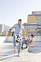 Friends meeting on rooftop terrace in summer, playing football - WESTF23121