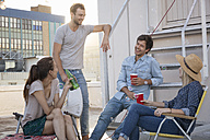 Friends having a rooftop party on a beautiful summer evening - WESTF23133
