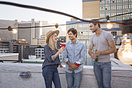 Friends having a rooftop party on a beautiful summer evening - WESTF23136