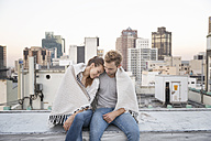 Romantic couple sitting on rooftop terrace, enjoying the view - WESTF23148