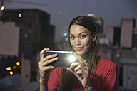 Young woman taking pictures of friends at a rooftop party - WESTF23157