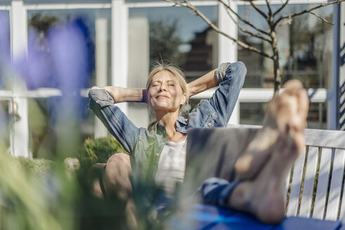 Smiling woman with laptop relaxing on garden bench - JOSF00771
