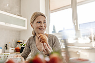Woman at home eating a croissant - JOSF00783