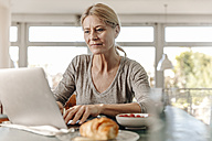 Woman at home having breakfast and using laptop - JOSF00792