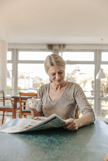 Woman at home sitting at table with cup of coffee and newspaper - JOSF00795