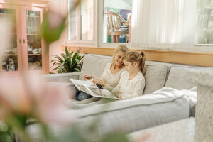 Mature woman and girl at home looking at photo album on couch - JOSF00798