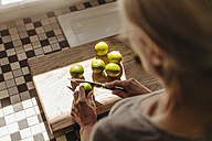 Woman in kitchen cutting limes - JOSF00801
