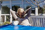 Woman relaxing on garden bench - JOSF00813