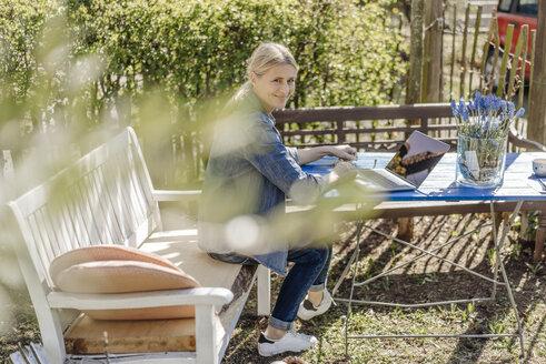 Smiling woman using laptop on garden bench - JOSF00816