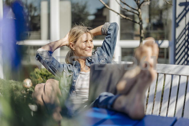 Smiling woman with laptop relaxing on garden bench - JOSF00819 - Joseffson/Westend61