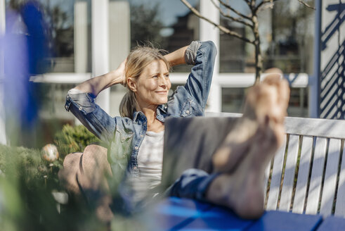 Smiling woman with laptop relaxing on garden bench - JOSF00819
