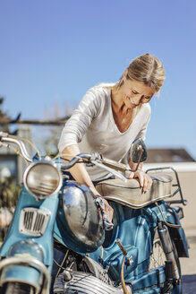 Smiling woman cleaning vintage motorcycle - JOSF00822