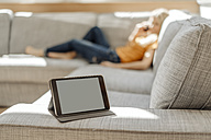 Tablet on couch with relaxed woman in background - JOSF00825