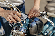 Close-up of woman cleaning vintage motorcycle - JOSF00828