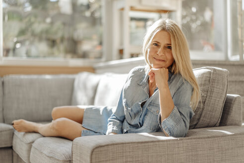 Portrait of smiling woman at home on couch - JOSF00831