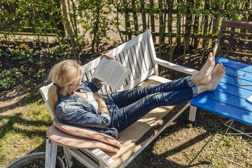 Woman reading book on garden bench - JOSF00840