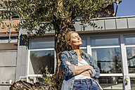 Woman in garden leaning against a tree - JOSF00843