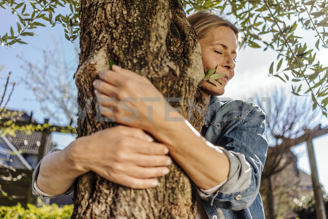 Woman in garden hugging a tree - JOSF00846
