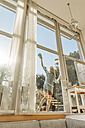 Woman cleaning the window in sunshine - JOSF00855