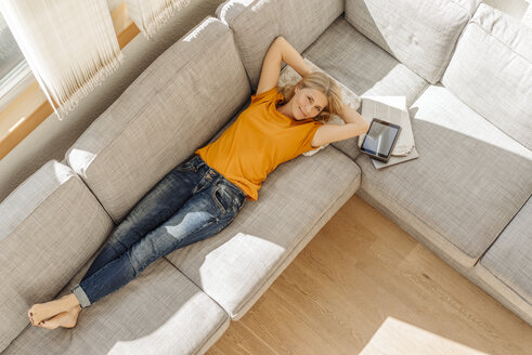 Smiling woman at home lying on couch - JOSF00861