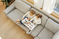 Mature woman and girl at home looking at photo album on couch - JOSF00864