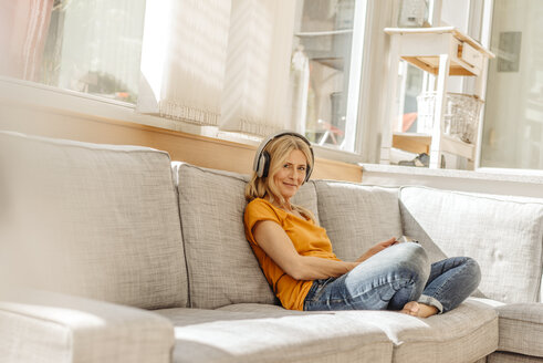 Woman at home sitting on couch wearing headphones - JOSF00870