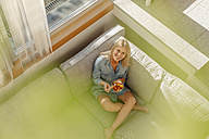 Happy woman at home sitting on couch eating fruit salad - JOSF00876