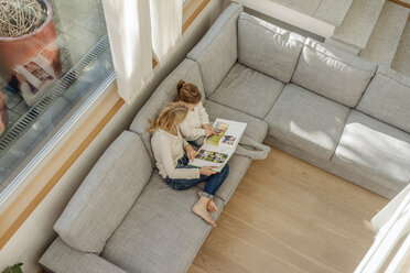Mature woman and girl at home looking at photo album on couch - JOSF00891
