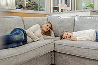 Mature woman and girl at home lying on couch - JOSF00894