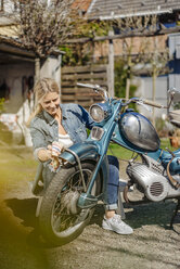 Smiling woman cleaning vintage motorcycle - JOSF00903