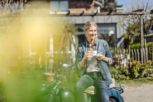 Smiling woman on vintage motorcycle having a coffee break - JOSF00906