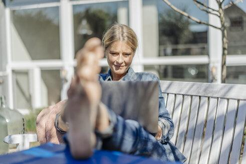 Smiling woman using laptop in garden - JOSF00909