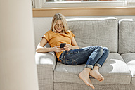 Woman at home on couch using cell phone - JOSF00912