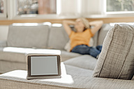 Tablet on couch with relaxed woman in background - JOSF00915
