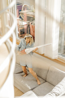 Playful woman at home wearing headphones using vacuum cleaner as air guitar on the couch - JOSF00930