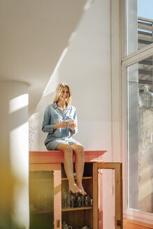 Happy woman at home sitting on cupboard with cup of coffee - JOSF00933